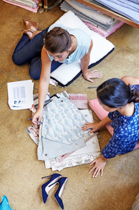 High angle view of interior designers choosing curtain samples while sitting on floor in workshopの写真素材 [FYI03718465]