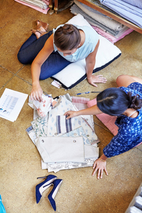 High angle view of interior designers selecting curtain samples while sitting on floor in workshopの写真素材 [FYI03718466]
