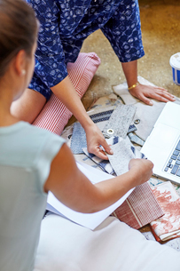 Cropped image of interior designers choosing curtain samples while sitting in workshopの写真素材 [FYI03718468]