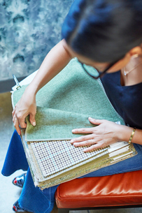 High angle view of interior designer looking at curtain samples while sitting in workshopの写真素材 [FYI03718473]