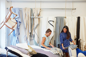Interior designers selecting curtain samples while standing in workshopの写真素材 [FYI03718478]