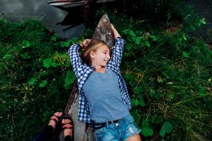 Overhead view of teenage girl lying on ship's bow at lakeshoreの写真素材 [FYI03718733]