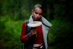 Teenage girl looking at large mushroom while standing in forestの写真素材 [FYI03718752]