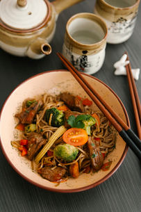 High angle view of noodles served in bowl with chopsticks on tableの写真素材 [FYI03718818]