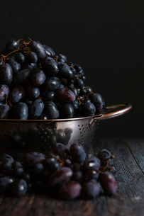 Close-up of grapes in colander on table against black backgroundの写真素材 [FYI03718819]