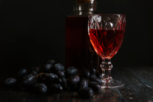 Red wine and grapes against black backgroundの写真素材 [FYI03718820]