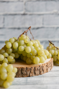 Close-up of grapes on wood against wallの写真素材 [FYI03718821]