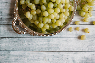 High angle view of grapes in container on wooden tableの写真素材 [FYI03718822]