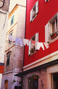 Low angle view of clothesline hanging on buildingの写真素材 [FYI03718847]