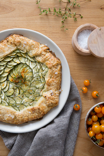 Overhead view of savory pie in plate with cherry tomatoes on tableの写真素材 [FYI03719015]