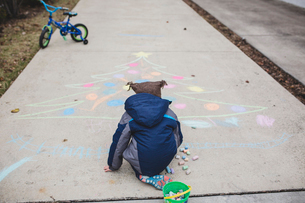 Rear view of boy in warm clothing drawing Christmas tree with chalks on footpathの写真素材 [FYI03719114]