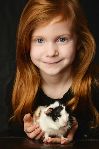 Close-up portrait of girl holding guinea pigの写真素材 [FYI03719313]
