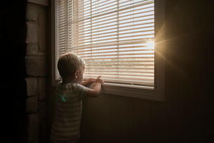 Boy playing with window blinds while standing at homeの写真素材 [FYI03719373]