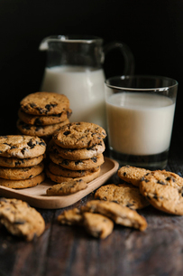 Close-up of cookies and milk on table against black backgroundの写真素材 [FYI03720564]