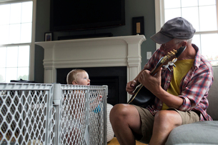 Grandson looking at grandfather playing string instrument at homeの写真素材 [FYI03720662]