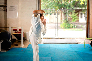 Side view of woman practicing taekwondo in gymの写真素材 [FYI03720715]