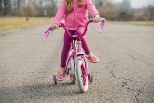 Low section of girl sitting on bicycle with training wheels on roadの写真素材 [FYI03722113]