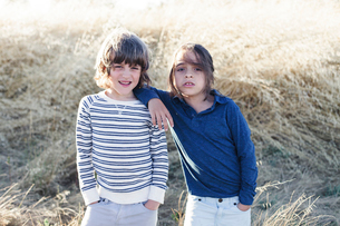 Portrait of brothers standing against heap of hay at fieldの写真素材 [FYI03722401]