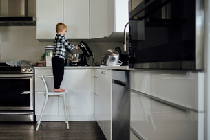 Full length of boy using electric mixer in kitchenの写真素材 [FYI03722683]