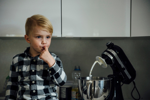 Cute boy tasting food from mixer in kitchenの写真素材 [FYI03722694]