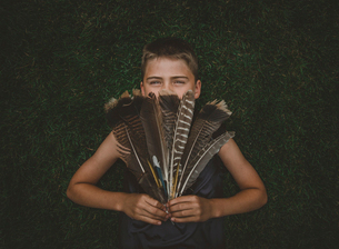 Portrait of boy holding feathers while standing against hedge at yardの写真素材 [FYI03722816]