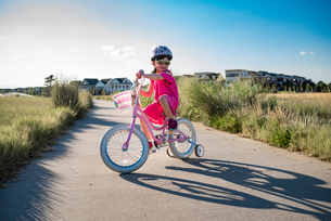 Girl riding bicycle with training wheels on road against sky during sunny dayの写真素材 [FYI03722864]