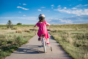 Rear view of girl sitting on bicycle with training wheels against sky during sunny dayの写真素材 [FYI03722865]