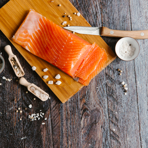 Close-up of salmon with spice on cutting board at tableの写真素材 [FYI03723111]