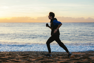 Side view of teenage boy listening music while jogging at beach against sea and cloudy skyの写真素材 [FYI03723246]