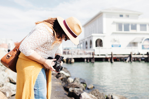 Side view of woman adjusting camera while standing by seaの写真素材 [FYI03723392]