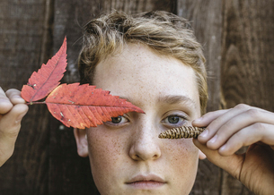 Close-up portrait of boy holding autumn leaves and pine cone against woodの写真素材 [FYI03723452]