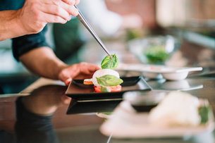 Close-up of man having caprese salad with chopsticksの写真素材 [FYI03723674]