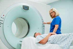 Nurse looking at patient lying on MRI Scanner while pressing start button in examination roomの写真素材 [FYI03723731]