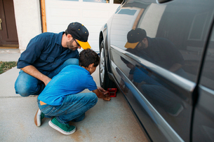 Father and son adjusting car stopper on wheel at drivewayの写真素材 [FYI03723950]