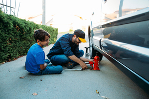 Father teaching son to use car jack while sitting at drivewayの写真素材 [FYI03723951]
