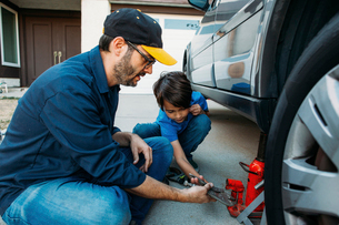 Father teaching son to use car jack at drivewayの写真素材 [FYI03723953]