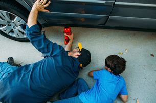 High angle view of father teaching son to use car jack at drivewayの写真素材 [FYI03723954]