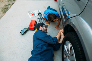 High angle view of father teaching son to repair car at drivewayの写真素材 [FYI03723960]