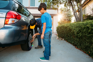 Son looking at father tightening tire with spanner at drivewayの写真素材 [FYI03723961]