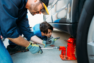Father guiding son while using car jack to repair car at drivewayの写真素材 [FYI03723966]