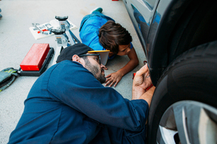 High angle view of serious father teaching son to repair car at drivewayの写真素材 [FYI03723967]