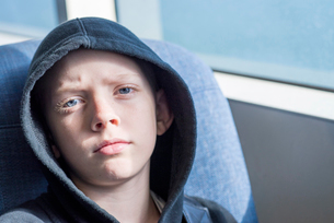 Close-up portrait of confident boy wearing hooded shirt in busの写真素材 [FYI03723978]