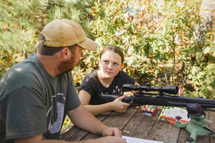 High angle view of daughter looking at father while holding rifle at backyardの写真素材 [FYI03723989]