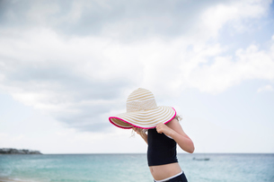 Side view of girl holding hat while standing against sea and cloudy sky at beachの写真素材 [FYI03723994]
