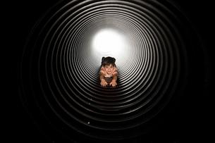 Portrait of playful boy lying in huge metallic pipeの写真素材 [FYI03724085]