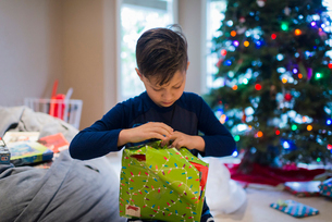 Boy wrapping Christmas present while sitting at homeの写真素材 [FYI03724134]