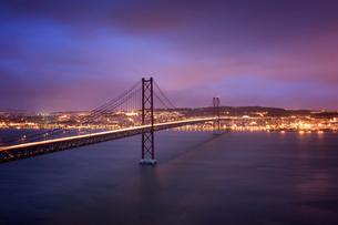 Light trails on April 25th Bridge over Tagus River against cloudy sky in illuminated city at nightの写真素材 [FYI03724306]