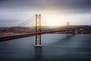Light trails on April 25th Bridge over Tagus River against cloudy sky during sunsetの写真素材 [FYI03724307]