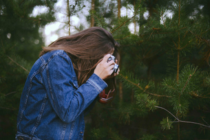 Side view of woman photographing pine trees in forestの写真素材 [FYI03724496]