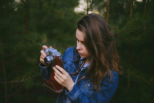 Woman photographing pine trees in forestの写真素材 [FYI03724500]
